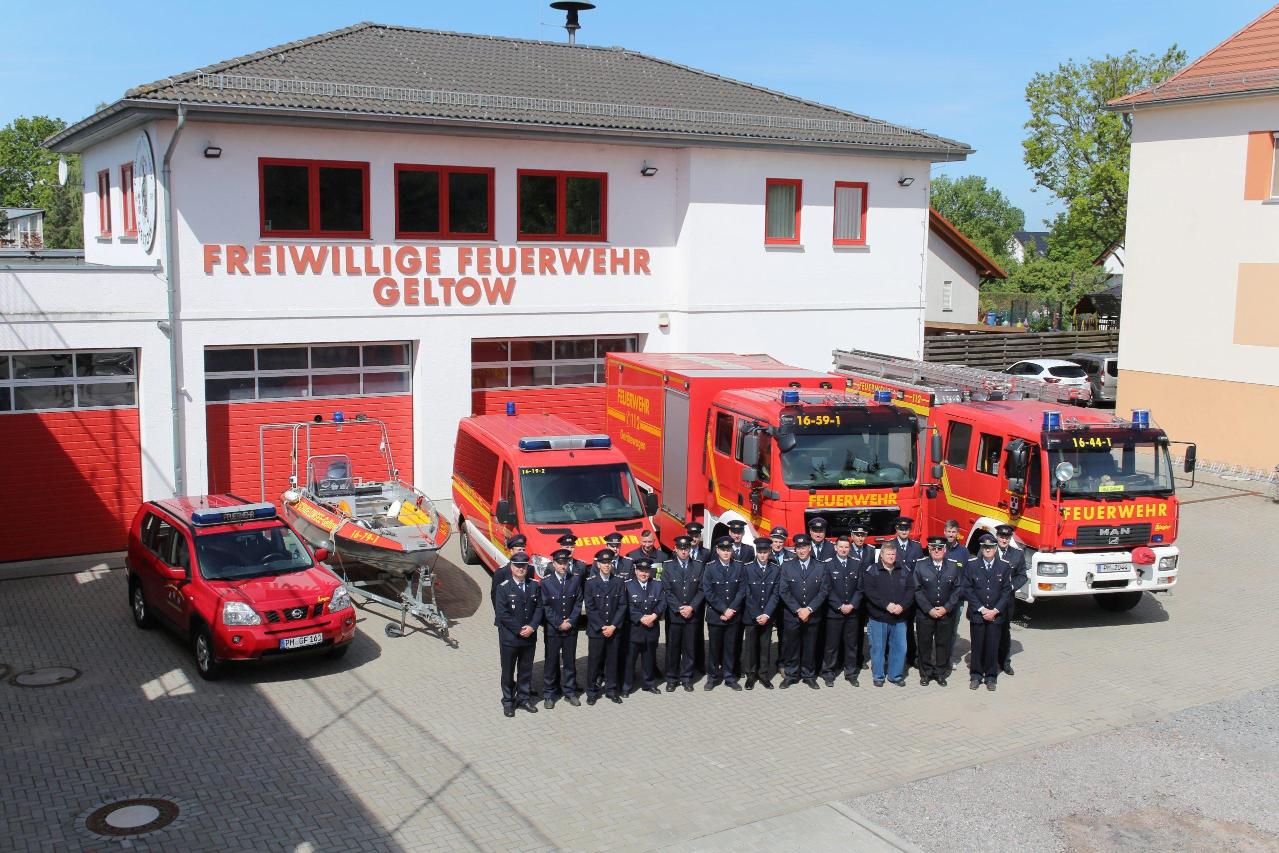 Gruppenfoto aller Kameraden der Feuerwehr, in Uniform vor den Fahrzeugen.